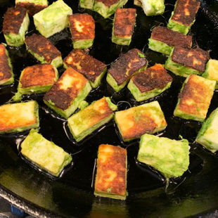 paneer pieces being pan fried on a skillet