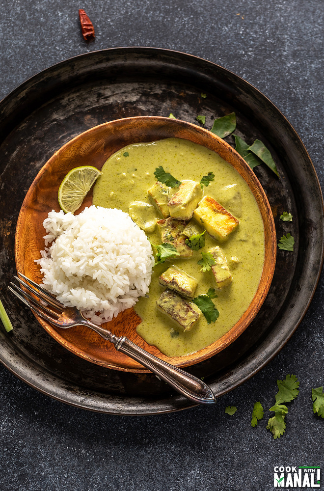 green color curry served with rice on a wooden plate