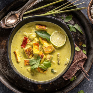 paneer lemongrass coconut curry served in a black bowl with stalks of lemongrass placed in the background and garnished with lime wedge