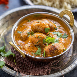 dum aloo served in a copper kadai garnished with cilantro with a plate of rice in the background