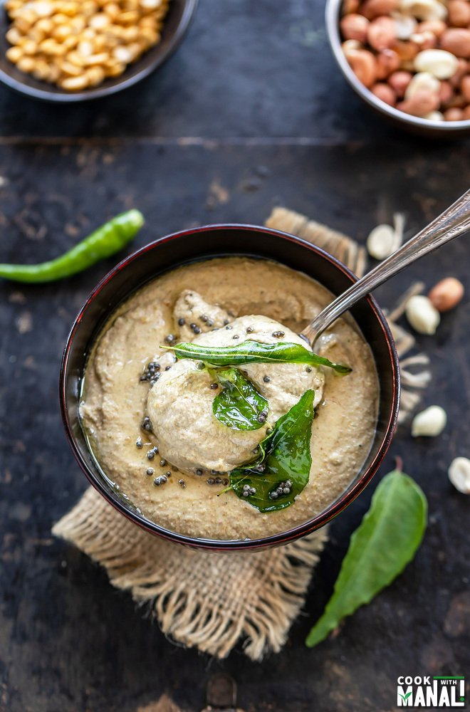 a spoon scooping out peanut chutney from a wooden bowl with few curry leaves and peanuts scattered on the sides