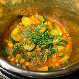 zucchini and chickpea in a tomato based curry garnished with cilantro