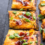 three slices of pizza topped with cilantro and chutney and placed on a black board