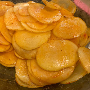 thinly sliced potatoes coated with spices