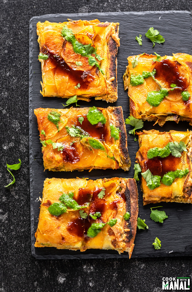 5 slices of pizza arranged on a black board, the slices are topped with chutneys and cilantro
