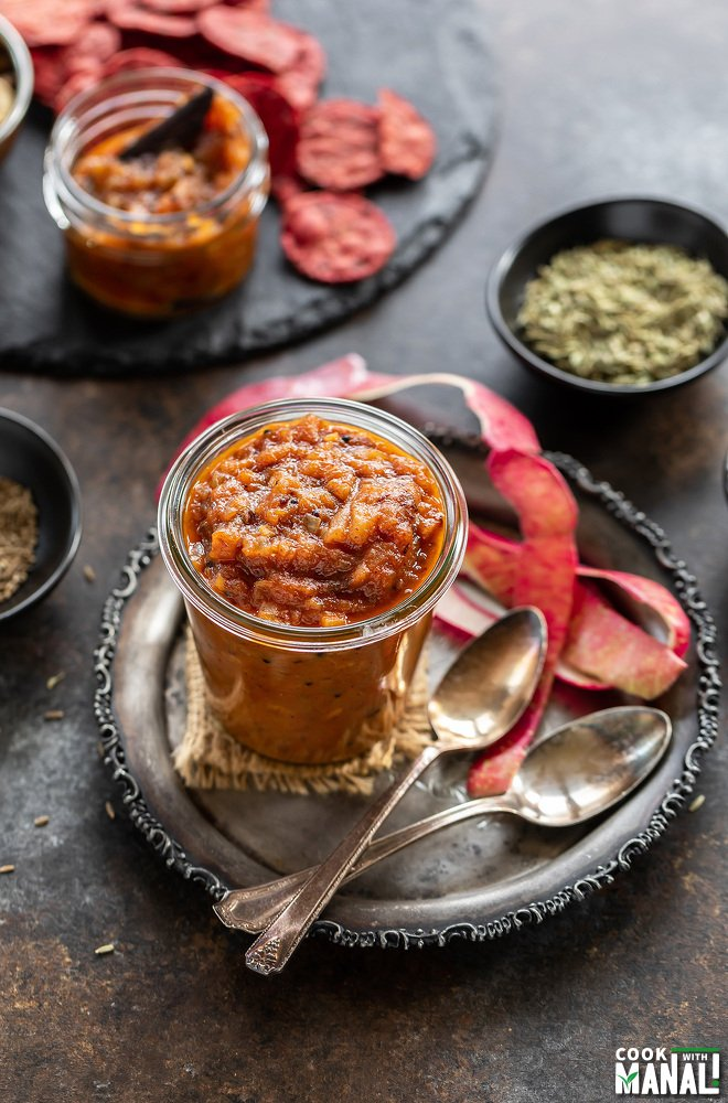 apple chutney in a glass jar with apple peel placed on the side and few spice bowls in the background