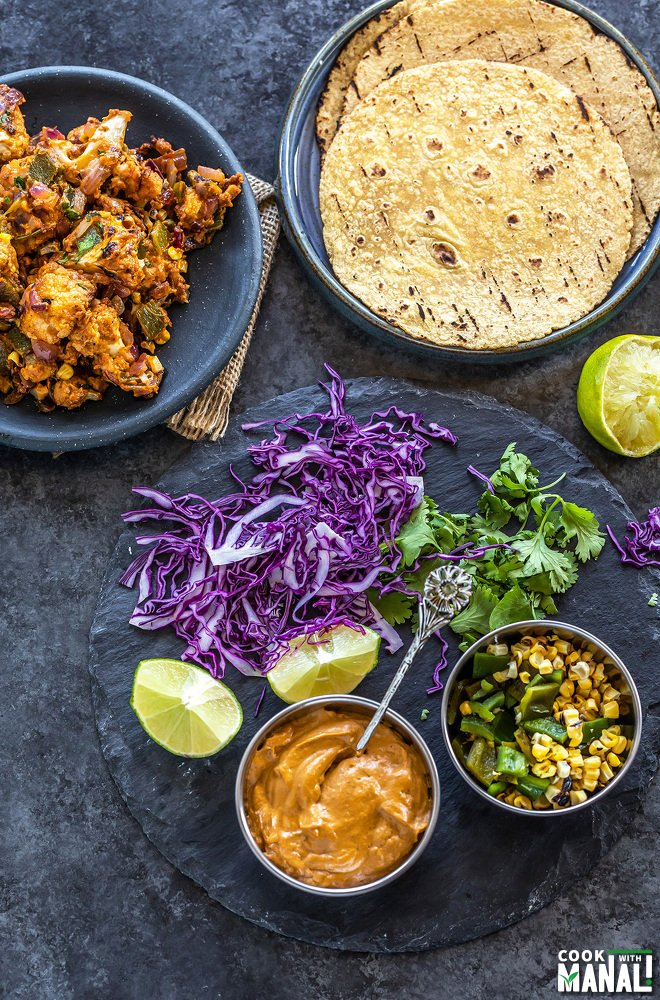 a plate with tortillas and another with cauliflower with 2 bowls filled with sauce and roasted corn and some purple cabbage, cilantro and lime placed on the sides