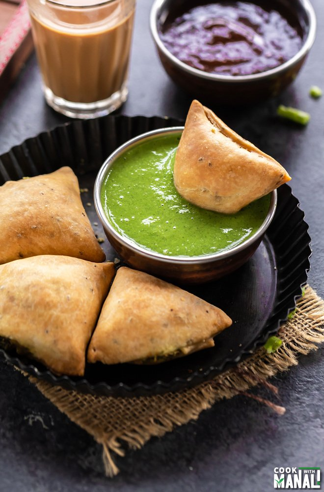 samosa dipped in a bowl of cilantro chutney