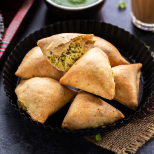 7 baked samosa arranged on a plate with glass of chai on the side and bowl of cilantro chutney in the background