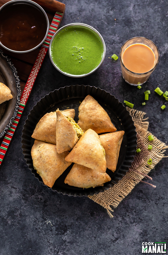 plate of baked samosa and bowls of chutney in the background and a glass of chai on the side