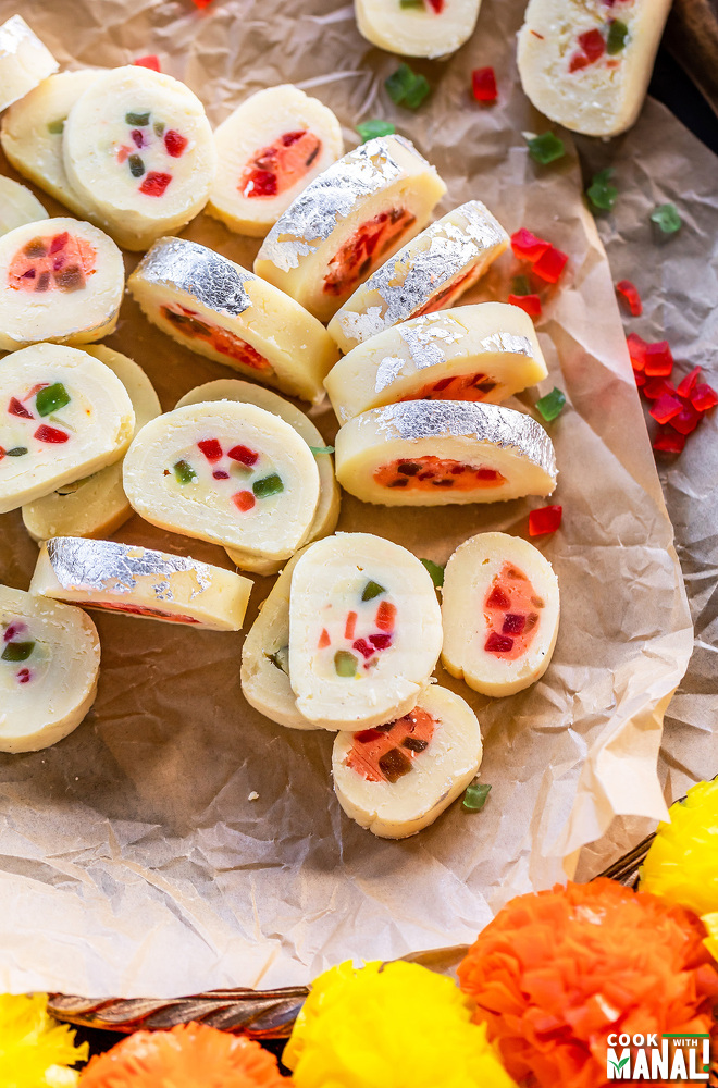 plate of sliced burfi roll with some artificial flowers on sides