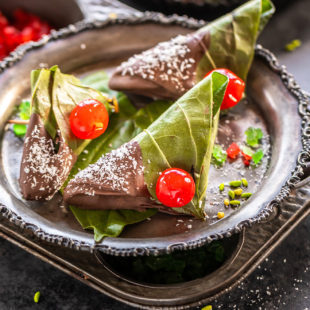 3 chocolate paan topped with cherries and placed in a antique plate