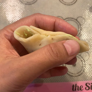hands pinching a samosa to seal it
