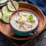 bowl of cucumber raita in a blue bowl garnished with mint leaves and spices and few round slices of cucumber in the background