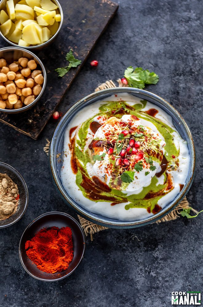 raj kachori placed in a plate garnished with pomegranate, cilantro and bowls of potatoes, chickpeas and spices placed on the side and background