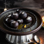 kala jamun arranged on an antique plate with some lights in the background