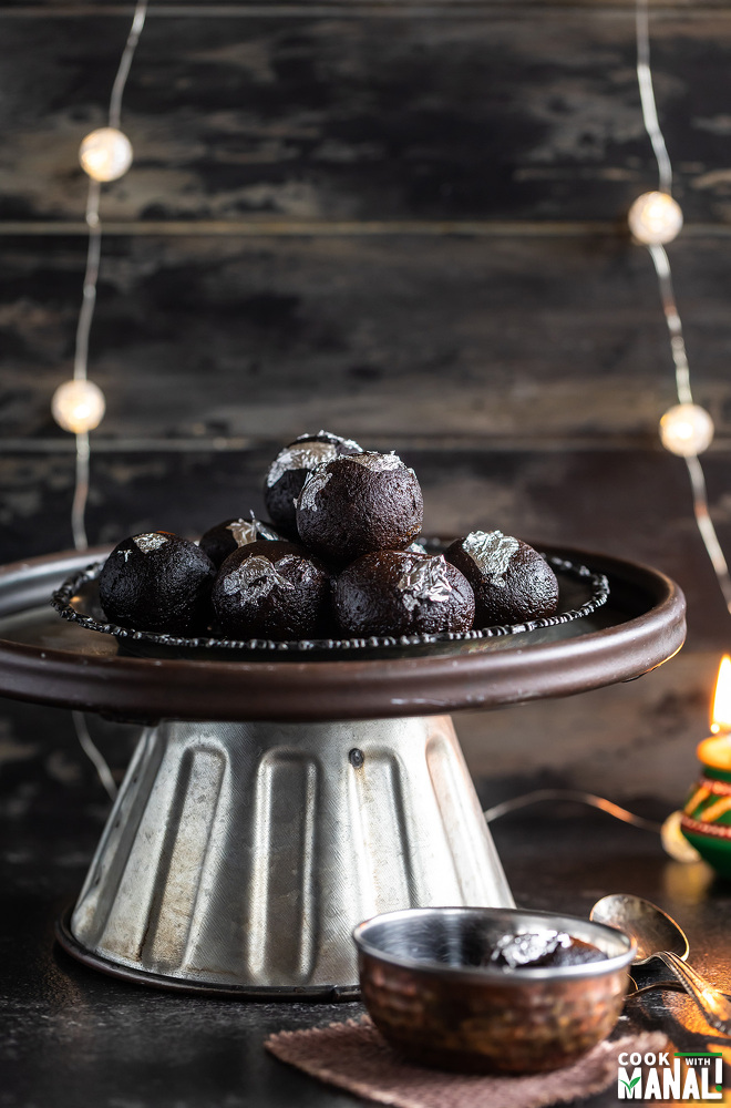 kala jamuns arranged in a plate and place of a cake stand with strings of lights in the background