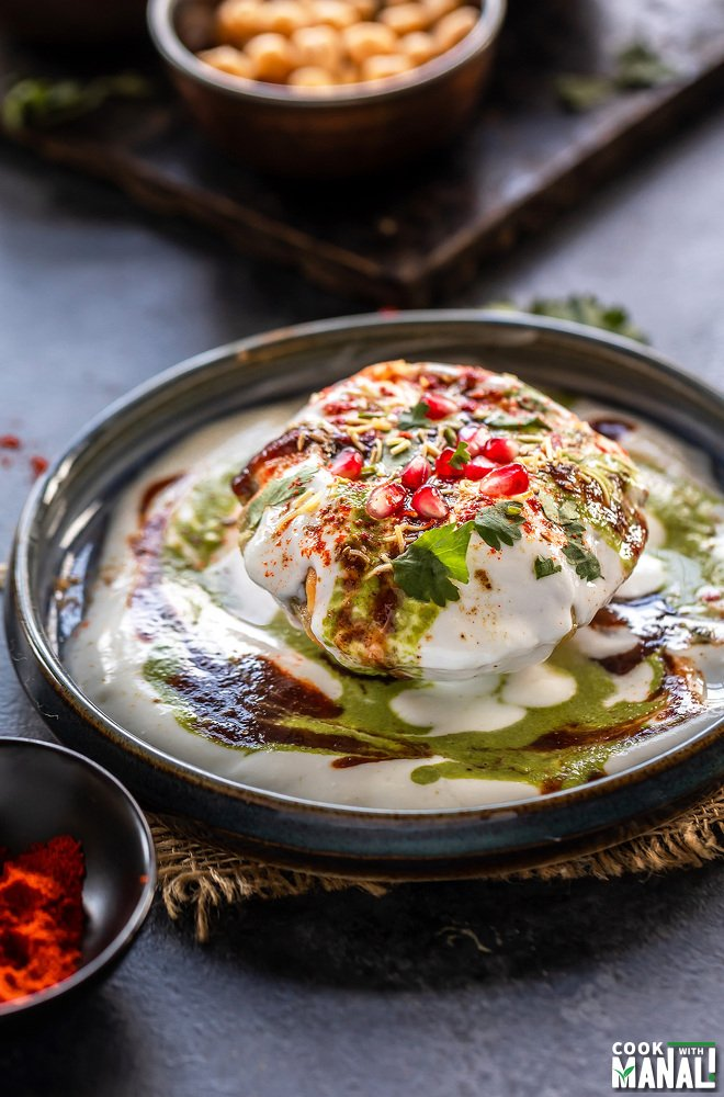 raj kachori placed on a plate topped with yogurt, chutney, pomegranate, cilantro and bowl of spices placed in the background