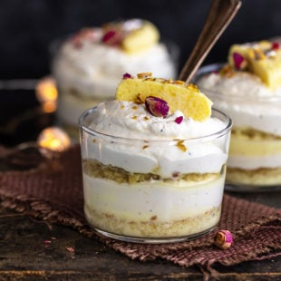 3 rasmalai cake jars placed on a board with lights in the background