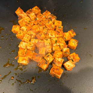 marinated paneer pieces being cooked on a griddle