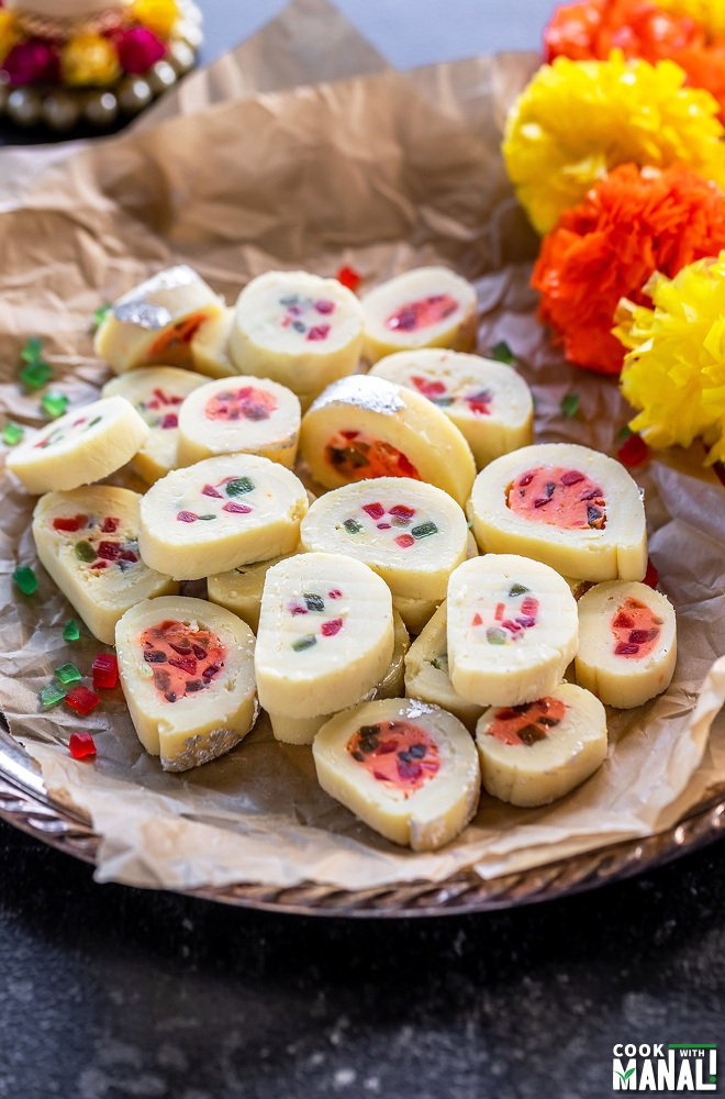 plate of burfi rolls with flowers placed on the side