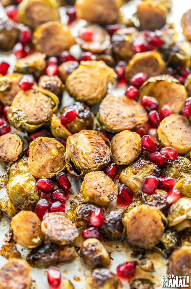 roasted brussel sprouts in a baking pan with pomegranate