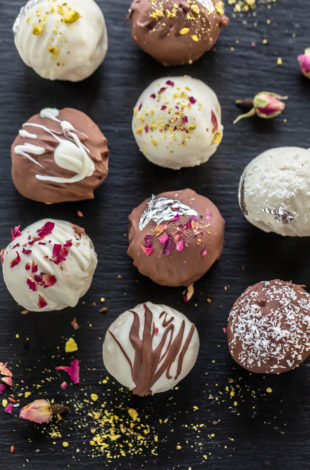 burfi truffles topped with nuts, rose petals arranged on a black board
