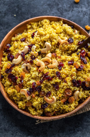 plate of saffron quinoa topped with roasted cashews, raisins and cranberries