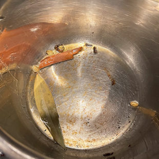 whole spices like bay leaves, cinnamon stick in a pot