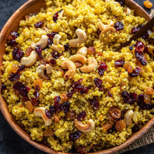 cooked saffron quinoa topped with nuts and raisins