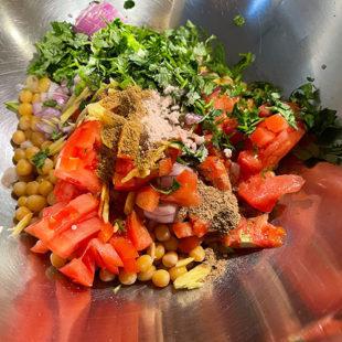 bowl with chopped onion, tomato, cilantro, white peas and spices