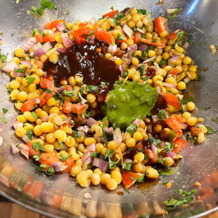 bowl of white peas mixed with onions, tomatoes, spices and topped with chutneys
