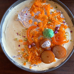 a cheesecake topped with Indian sweets like ladoo, gulab jamun, jalebi