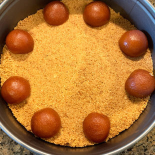 sliced gulab jamuns arrange on top of cookie crust in a pan