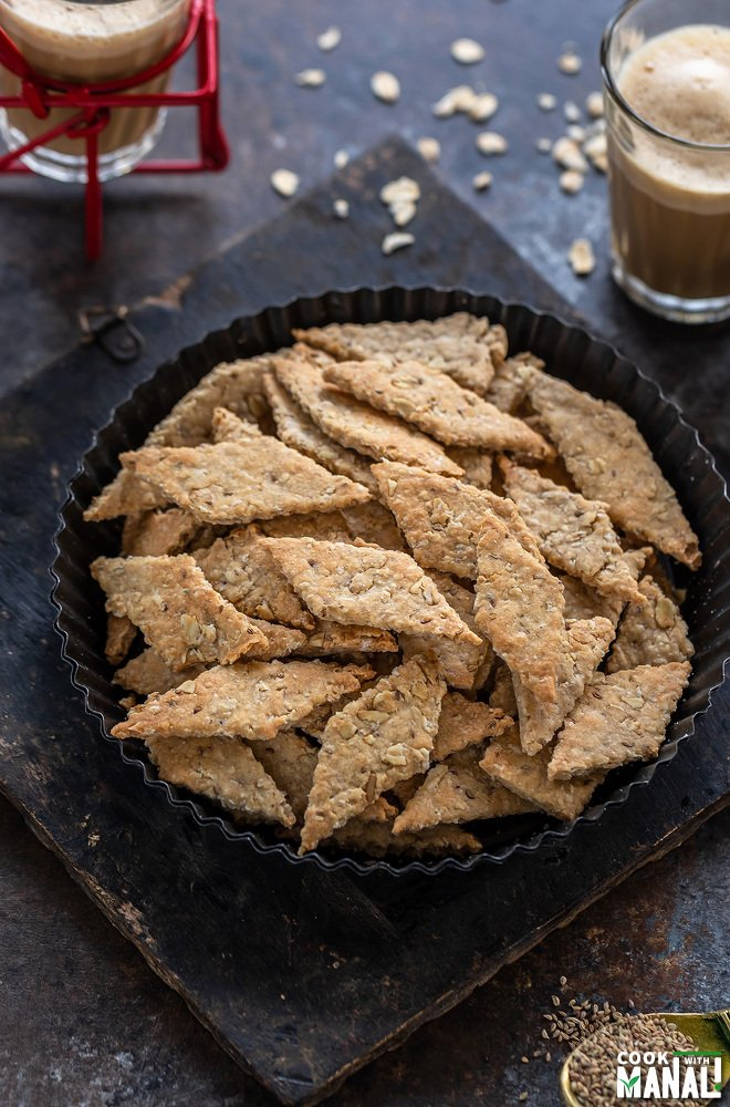 diamond shaped oats namak pare placed in a round plate with glass of chai in the background