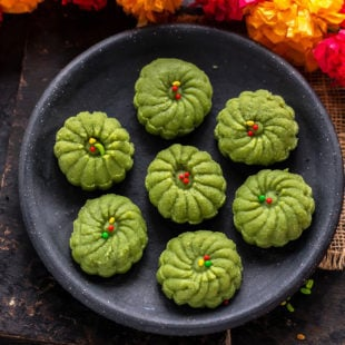7 paan peda arranged on a plate with a chain of flowers on the side