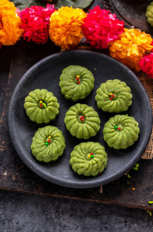 7 paan peda arranged on a plate with string of flower on the side
