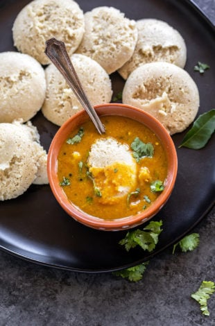 bowl of sambar with idli dipped into it and more idlis placed on the plate