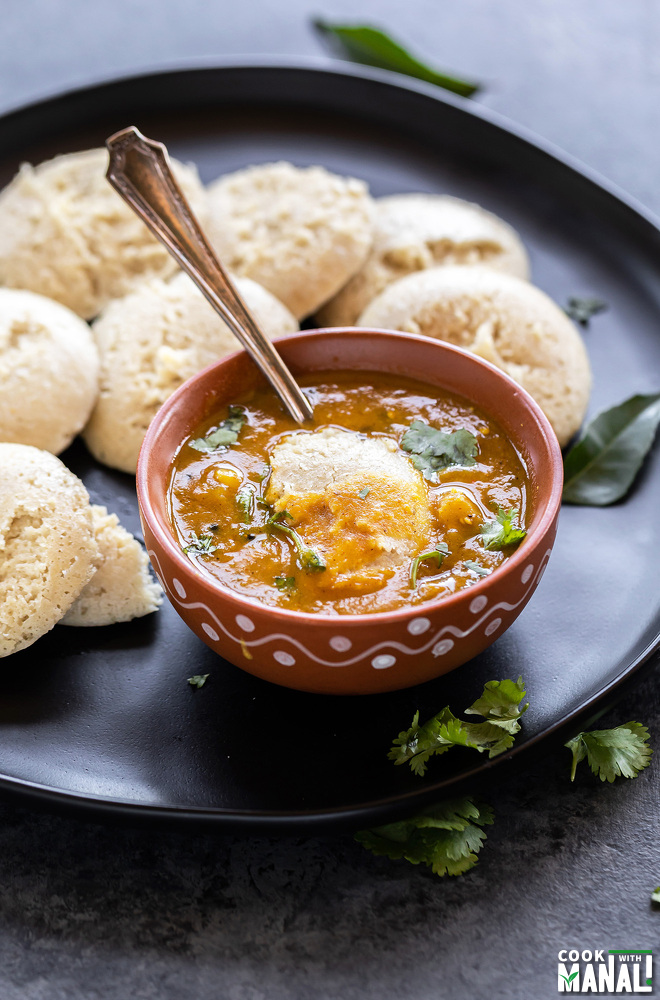 broken idli dunked in a bowl of sambar with more idlis in the background