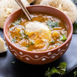 idli dunked in a bowl of sambar