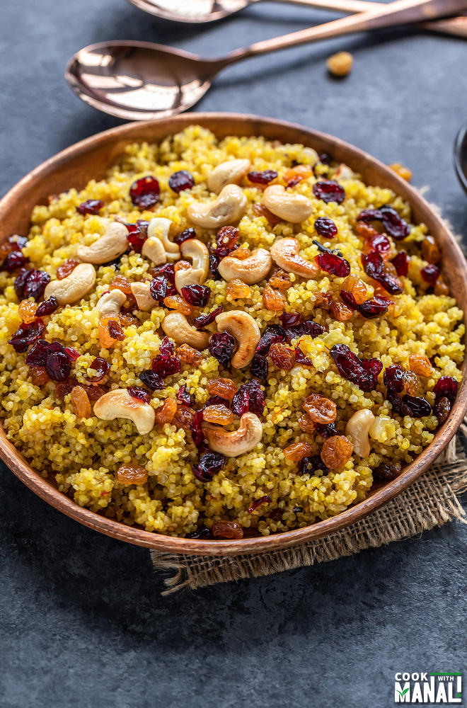 plate full of saffron quinoa topped with nuts and raisins and spoons placed in the background