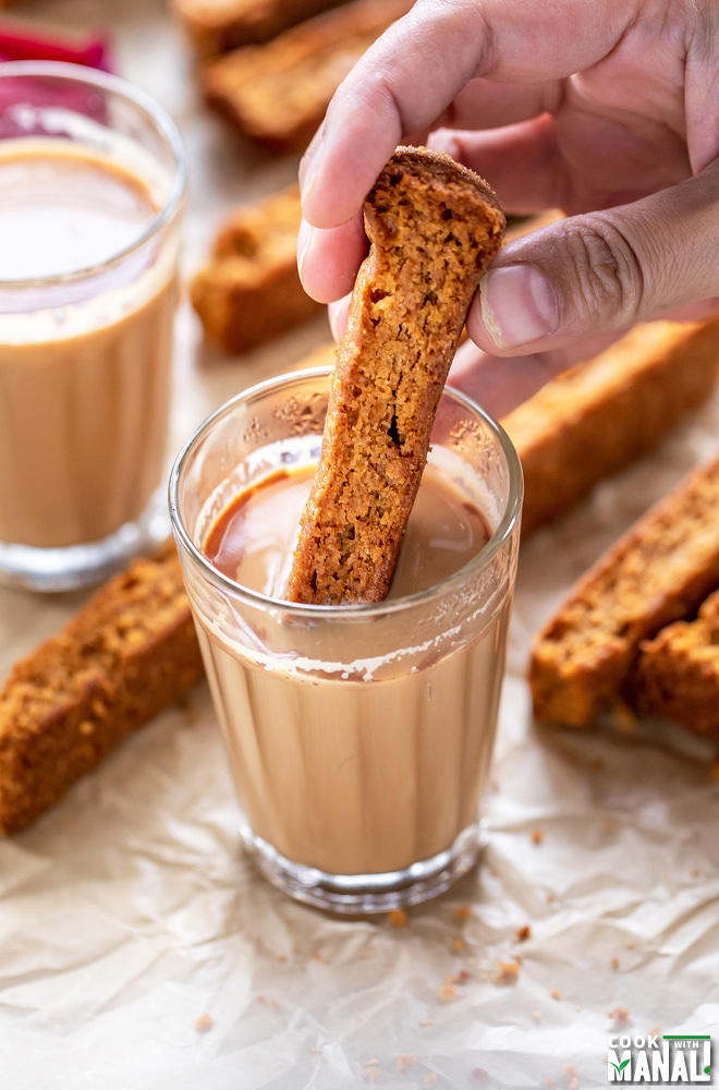 a hand dipping rusk in a glass of chai