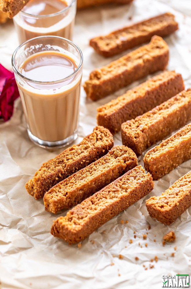some rusk arranged on a tray with chai glasses in the background