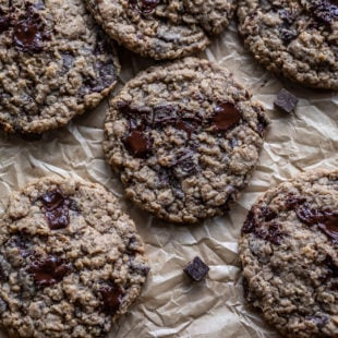 eggless oatmeal chocolate chunk cookies arranged on top of a parchment paper on a baking tray