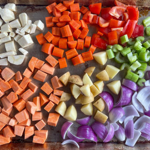 chopped sweet potatoes, red pepper, onion, potatoes, celery placed in a baking tray