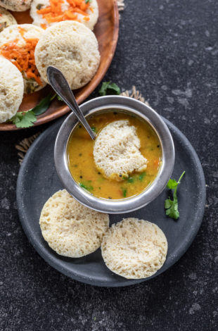 3 dal idli in a plate with 1 dipped in bowl of sambar