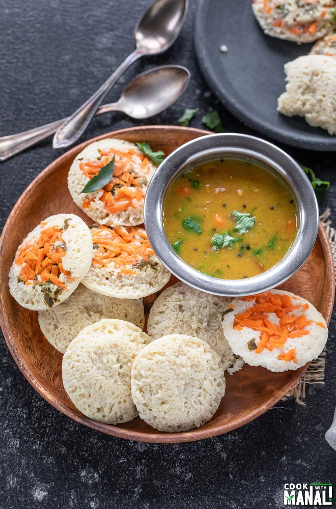 plate of idlis with sambar with 2 spoons placed in back