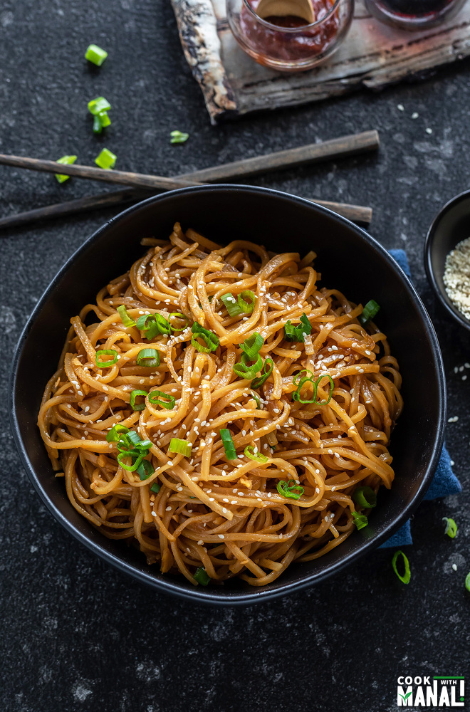 bowl of noodles with chopsticks placed on the side