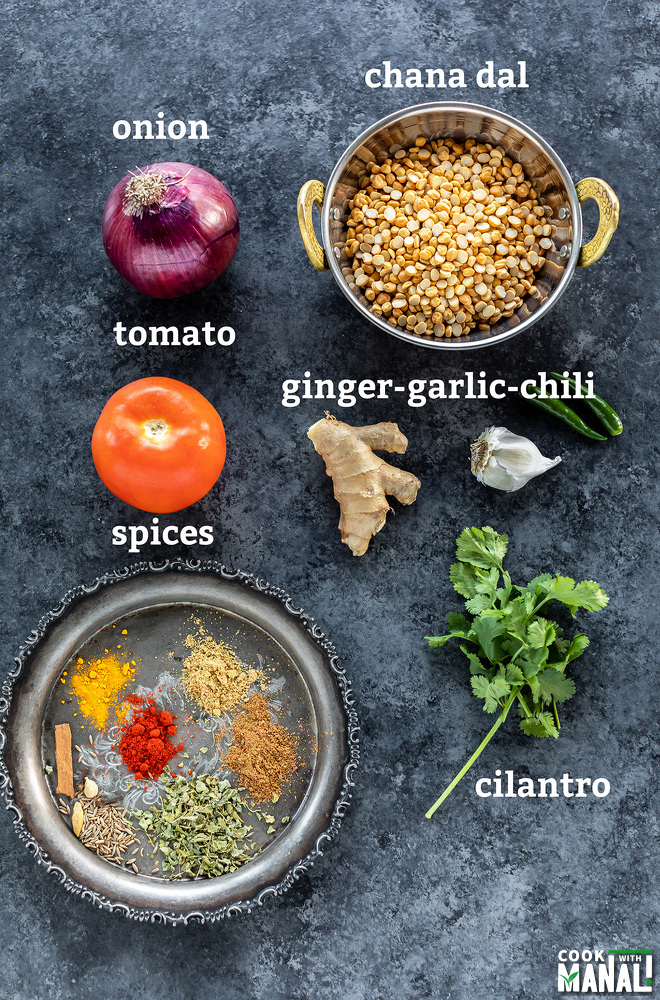 lentil, spices, onion, ginger, garlic, tomatoes placed on a board