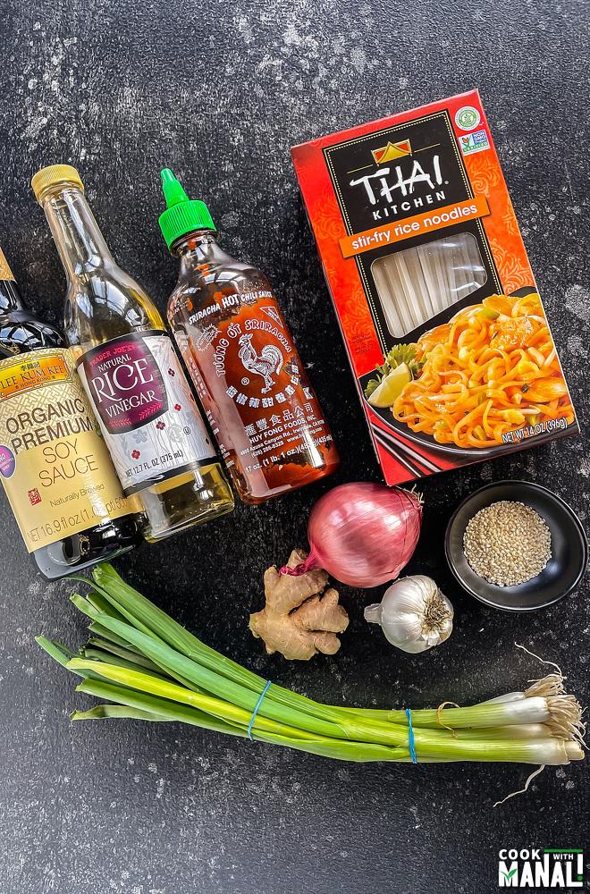 bottles of soy sauce, hot sauce, vinegar, packet of noodles, garlic-ginger arranged together